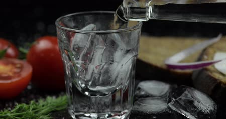 tomates cereja : Pouring up shot of vodka with ice cubes from a bottle into glass. Bread with lard, onion, dill and cherry tomatoes against black background. Close-up. Pour of alcohol drink Vídeos
