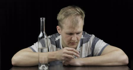 smutek : Depressed man pour vodka in a shot glass drinking alone in a dark room. Drinking from a bottle. Concept of alcoholism. Close-up shot