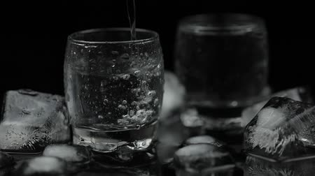 bekap : Pouring up shot of vodka from a bottle into glass against black background with ice cubes. Pour of alcohol drink vodka tequila. Slow motion Stock mozgókép