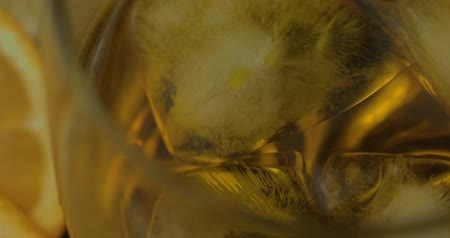 pálinka : Whiskey with ice in drinking glass. Close-up shot of ice cubes float. Glass of rum alcohol close-up Stock mozgókép