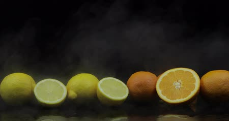 cítrico : Tropical lemon and orange in cold ice clouds of fog smoke on black background. Fresh and tasty fruits