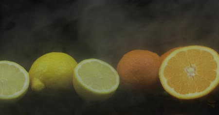 lemoniada : Tropical lemon and orange in cold ice clouds of fog smoke on black background. Fresh and tasty fruits