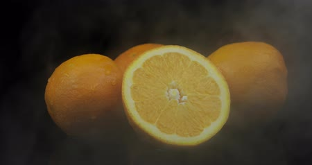 jus d orange : Tropical fruit orange in cold ice clouds of fog smoke on black background. Fresh and tasty fruits