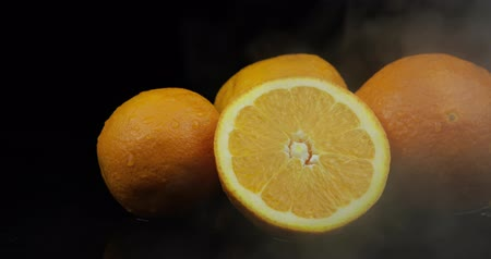 vitamine c : Tropical fruit orange in cold ice clouds of fog smoke on black background. Fresh and tasty fruits
