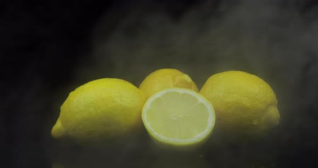 cítrico : Tropical fruit lemon in cold ice clouds of fog smoke on black background. Fresh and tasty fruits