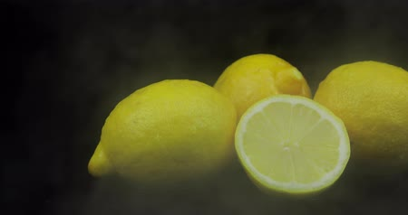 citrico : Tropical fruit lemon in cold ice clouds of fog smoke on black background. Fresh and tasty fruits