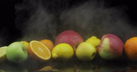 лимонный : Tropical lemon, orange, apple in cold ice clouds of fog smoke on black background. Fresh and tasty fruits. Concept of healthy and rich in vitamins food
