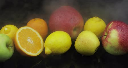 cítrico : Tropical lemon, orange, apple in cold ice clouds of fog smoke on black background. Fresh and tasty fruits. Concept of healthy and rich in vitamins food