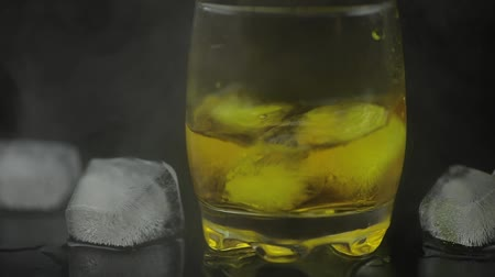 single shot : Whiskey with ice. Adding ice cubes on black background with cold ice clouds of fog smoke. Glass of rum alcohol close-up. Isolated on black.