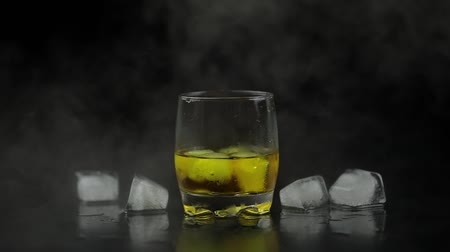 maltês : Whiskey with ice. Adding ice cubes and pouring whisky from the bottle on black background with cold ice clouds of fog smoke. Glass of rum alcohol close-up. Isolated on black. Slow motion