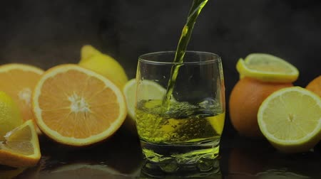 tonikum : Pour juice into glass, orange and lemon slices. Cocktail juice on black background with cold ice clouds of fog smoke. Refreshing alcoholic cocktail drink. Slow motion Dostupné videozáznamy