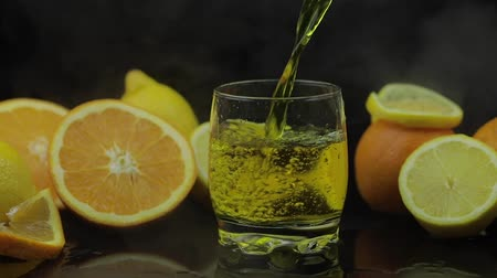 tomilho : Pour juice into glass, orange and lemon slices. Cocktail juice on black background with cold ice clouds of fog smoke. Refreshing alcoholic cocktail drink. Slow motion Stock Footage