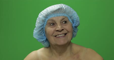 kalap : Smiling elderly female in protective hat looking to camera, plastic surgery. Green screen. Chroma key