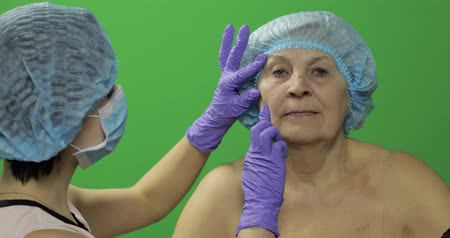 kalap : Smiling elderly female in protective hat. Plastic surgeon doctor checking woman face before cosmetic surgery. Dermatology. Green screen. Chroma key