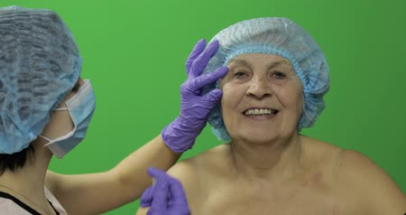 plastische chirurgie : Smiling elderly female in protective hat. Plastic surgeon doctor making facial injections for aging female patient, dermatology. Cosmetic surgery. Green screen. Chroma key