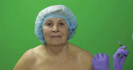 kalap : Smiling elderly female in protective hat. Plastic surgeon doctor making facial injections for aging female patient, dermatology. Cosmetic surgery. Green screen. Chroma key