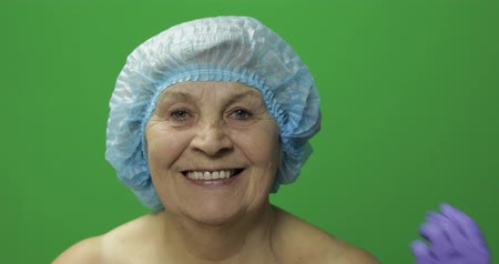 kalap : Smiling elderly female in protective hat. Plastic surgeon doctor hands making facial injections for aging female patient, dermatology. Cosmetic surgery. Green screen. Chroma key