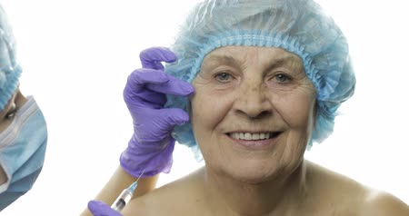 kalap : Smiling elderly female in protective hat. Plastic surgeon doctor hands making facial injections for aging female patient, dermatology. Cosmetic surgery. White background