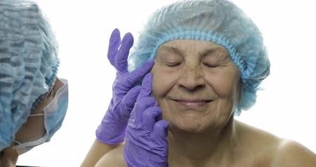 kalap : Smiling elderly female in protective hat. Plastic surgeon doctor checking woman face before cosmetic surgery. Dermatology. Doctor advises a patient who agrees with the suggestions. White background