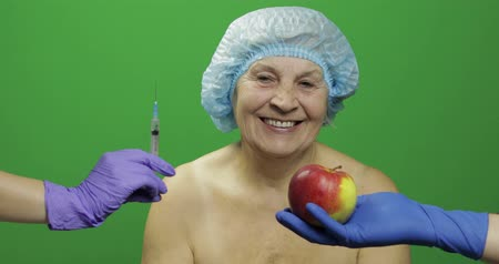 kalap : Smiling elderly female lady in protective hat. Woman chooses treats medications or fruits. Scared of syringe with medicines and liked an apple. Concept of healthy eating. Green screen. Chroma key Stock mozgókép
