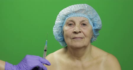 kalap : Smiling elderly female lady in protective hat scared of syringe with medicines. A woman is not satisfied with this way of treatment. Dermatology. Cosmetic surgery. Green screen. Chroma key Stock mozgókép