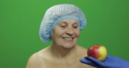 kalap : Smiling elderly female lady in protective satisfied with fruit way of treatment. Doctor shows her an apple and patient like this. Concept of healthy eating. Green screen. Chroma key