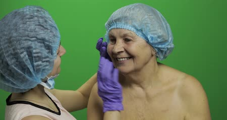 kalap : Smiling elderly female in protective hat. Plastic surgeon doctor checking woman face after cosmetic surgery. Dermatology. Doctor advises a patient who agrees with the suggestions. Chroma key