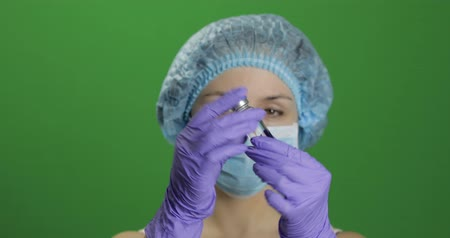 develop : Female scientist holding ampoule in hand, new medication developing, vaccination. Concept of medicine and health improvement. Chroma key background. Green screen