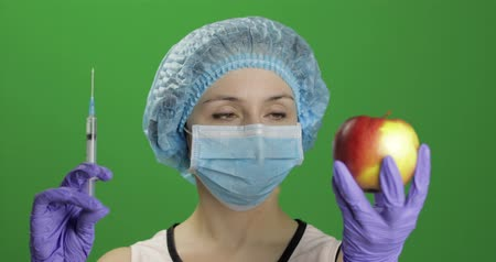 сущность : Female scientist holding syringe with medicines in one hand and an apple in other hand. She chooses syringe with medicines. Concept of medicine method of treatment. Chroma key background Стоковые видеозаписи