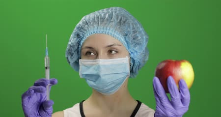 сущность : Female scientist holding syringe with medicines in one hand and an apple in other hand. She chooses an apple. Concept of medicine method of treatment with vitamins. Chroma key background