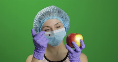 сущность : Female scientist holding syringe with medicines in one hand and an apple in other hand. She makes a injection with a medicine syringe in apple. Concept of genetic engineering. Chroma key background Стоковые видеозаписи