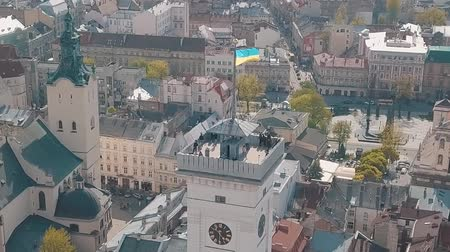 council of europe : Aerial Roofs and streets Old City Lviv, Ukraine. Central part of old city. Panorama of the ancient town. The Ukrainian flag flies on top of Town Hall, Ratush. Drone shot