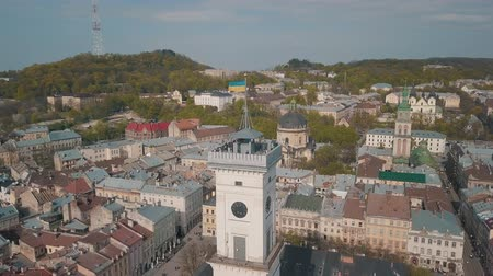 çatılar : Aerial Roofs and streets Old City Lviv, Ukraine. Central part of old city. European City in spring. Panorama of the ancient town. The Ukrainian flag flies on top of Town Hall, Ratush. Drone shot Stok Video