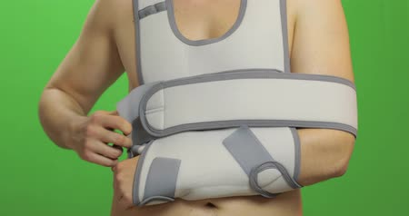 orthopédique : Man with shoulder injury. Patient in a bandage for fixing of an elbow joint and a humeral belt. Dislocations of arm of the forearm, shoulder. Broken bones. Arm brace