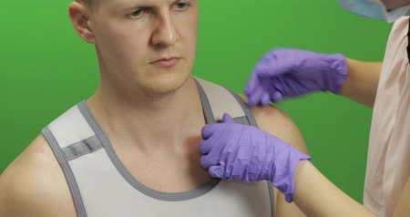 łokieć : Man with shoulder injury. Nurse wearing to patient a bandage for fixing of an elbow joint and a humeral belt. Dislocations of arm of the forearm, shoulder. Broken bones.