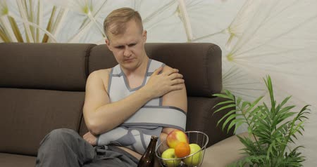 dişli : Man with shoulder injury. Painful, bored man with a broken arm wearing arm brace sitting on a sofa and drinks beer at home. Patient in a bandage for fixing of an elbow joint and a humeral belt