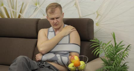 orthopédique : Man with shoulder injury. Painful, bored man with a broken arm wearing arm brace sitting on a sofa and eating apple at home. Patient in a bandage for fixing of an elbow joint and a humeral belt Vidéos Libres De Droits
