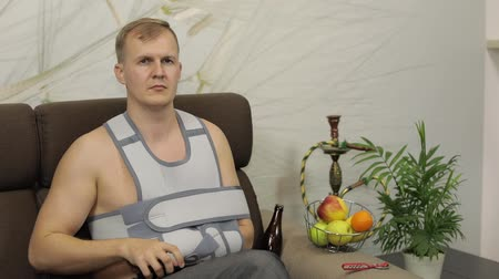 łokieć : Man with shoulder injury. Painful, bored man with a broken arm wearing arm brace sitting on a sofa at home watching TV. Patient in a bandage for fixing of an elbow joint and a humeral belt Wideo