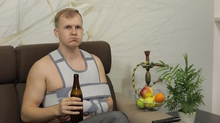 bandage : Man with shoulder injury. Painful, bored man with a broken arm wearing arm brace sitting on a sofa at home and drinks beer. Patient in a bandage for fixing of an elbow joint and a humeral belt Stock Footage