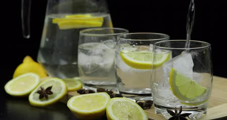 tápanyagok : Pour lemon juice into glass with ice and lemon slices. Lemon cocktail with ice on dark background. Refreshing alcoholic cocktail drink
