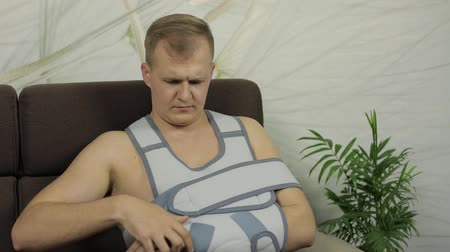 łokieć : Man with shoulder injury. Painful, bored man with a broken arm wearing arm brace sitting on a sofa at home. Patient in a bandage for fixing of an elbow joint and a humeral belt. Slow motion Wideo