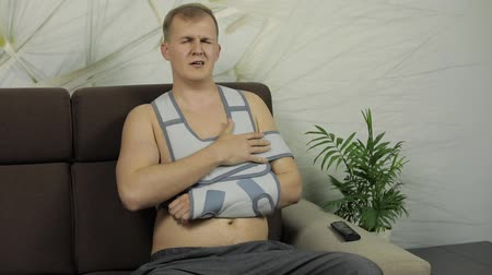 dişli : Man with shoulder injury. Painful, bored man with a broken arm wearing arm brace sitting on a sofa at home. Patient in a bandage for fixing of an elbow joint and a humeral belt. Slow motion Stok Video