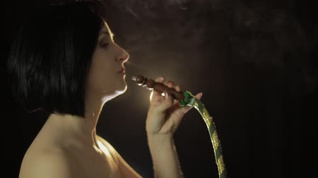 naga : Beautiful, young, naked woman smoking hookah. Attractive girl smoking flavored tobacco. Blow out smoke close-up on black background. Slow motion