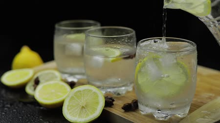 liquid : Pour lemon juice into glass with ice and lemon slices. Lemon cocktail with ice on dark background. Refreshing alcoholic cocktail drink. Slow motion