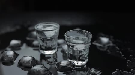 wódka : Add ice cubes to shot of vodka in glass against wet black background with ice cubes. Alcohol drink vodka tequila. Slow motion