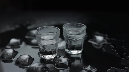 テキーラ : Add ice cubes to shot of vodka in glass against wet black background with ice cubes. Alcohol drink vodka tequila. Slow motion