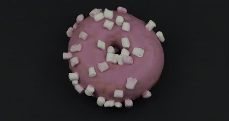 envidraçado : Delicious, tasty and fresh donut rotating. Top view. Bright and colorful sweet pink donut close-up macro shot spinning on a black background