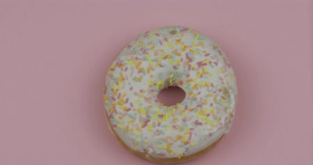 застекленный : Delicious, tasty and fresh donut rotating. Top view. Bright and colorful sprinkled white sweet donut close-up macro shot spinning on a pink background