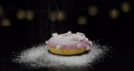 пончик : Tasty fresh pink donut lay on the black surface and gets sprinkle with icing sugar powder