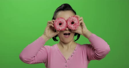 rosquinhas : Happy beautiful young girl on a chroma key background having fun with donuts. Cute woman in a pink shirt posing with donuts closes her eyes and smiling. Making faces Stock Footage